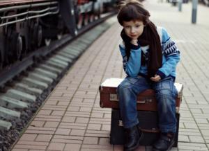 child sitting on suitcase